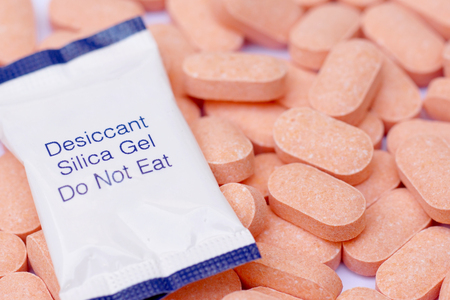 Desiccant pack on a pile of vitamin C tablets  Using silica gel with medicine to prevent humidity