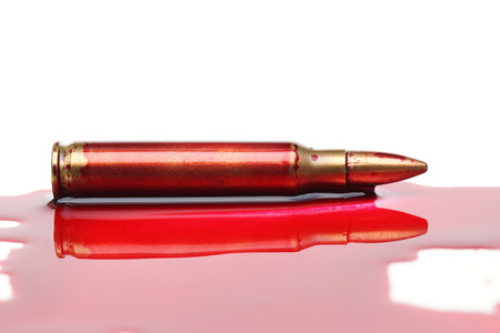 A rifle bullet with red blood  Bloodshed business  selling weapons causing death Stock Photo
