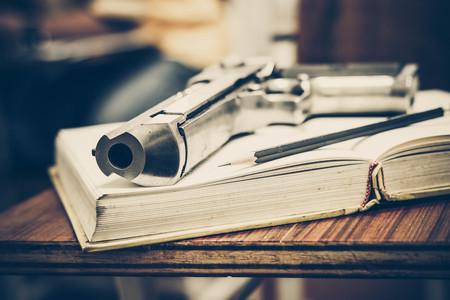 A gun on a textbook  Armed campus concept Stock Photo