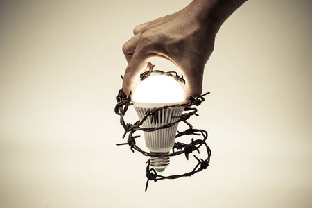 business innovation: Hand trying to catch a turned on LED light bulb with barbed wire  Something stops new idea  Freedom of thought and idea expression