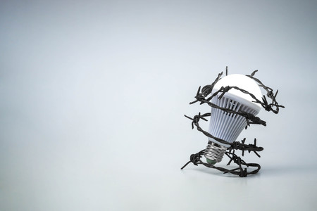 tortured: A turned on LED light bulb with barbed wire  Something stops new idea  Freedom of thought and idea expression