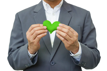 social behaviour: Businessman holding a green heart  Business with corporate social responsibility and environmental concern Stock Photo