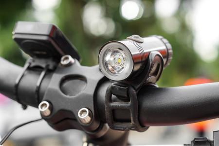 Luz delantera de bicicleta para montar de noche instalada en un manillar Foto de archivo