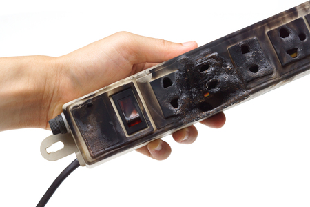 the protector: Hands holding a surge protector caught on fire due to overheat Stock Photo