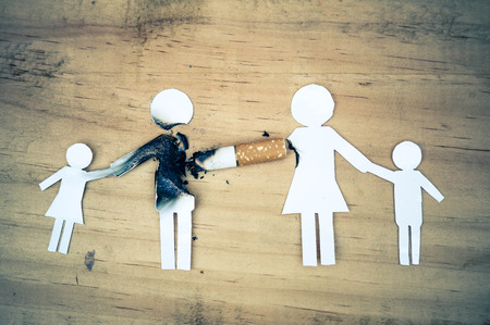 paper cut of family members destroyed by cigarettes / drugs destroying family concept / World no tobacco day