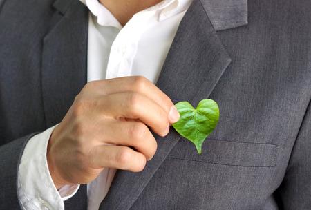Biznesmen gospodarstwa liści zielone serce / biznes z odpowiedzialności społecznej i troski o środowisko