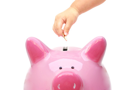 Hand of a young baby giving golden coin to a piggy bank  Young generation start saving for the future