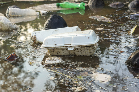 Water pollution - Plastic and foam garbage floating on the surface of the river - Environmental problem caused by human activity Stock Photo