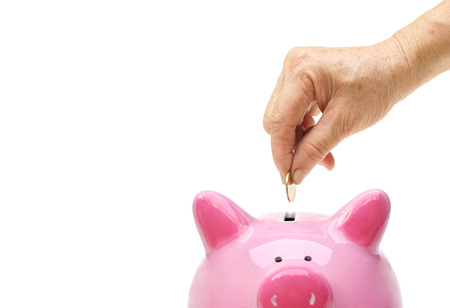 coin bank: Old hand putting a golden coin into a pink piggy bank  saving money for retirement concept Stock Photo