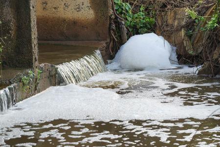 Watervervuiling - Afvalwater vol met bellen die vrijkomen uit de industriële gebieden en van invloed zijn op de natuurlijke watervoorraden
