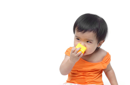 A young baby trying to put a small piece of toy into his mouth - The danger of young baby swallowing or eating little things concept