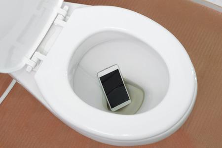 Een witte smartphone gedaald in een toiletpot Stockfoto - 68882835