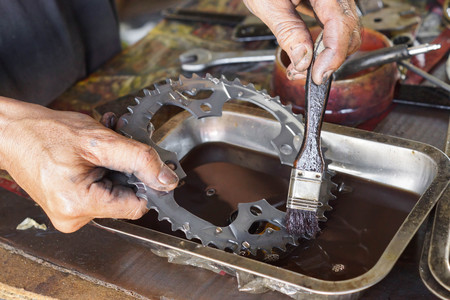 dientes sucios: Mechanic hand cleaning front chain ring