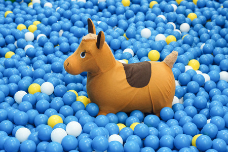 big ball: Rocking horse for kid in a big ball pit Stock Photo