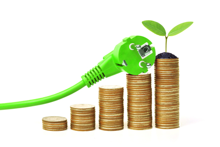 A green electricity plug with stack of golden coins and a green plant  Green energy creating wealth concept