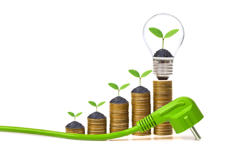 A green electricity plug with stack of golden coins and a young plant in a lightbulb / Green energy creating wealth concept Standard-Bild