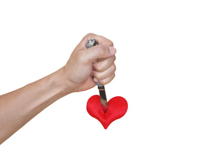 hand with a knife stabbing into a red heart Stock Photo
