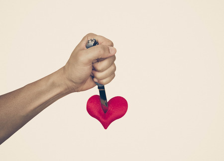 stabbing: hand with a knife stabbing into a red heart Stock Photo