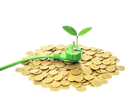 Green plug with a young green plant on golden pile of coins  Green energy create wealth and sustainability concept Stock Photo