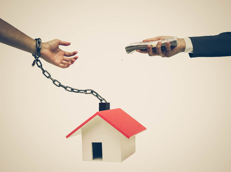 Hand of a businessman offering money to hand chained with a house  Buying a house causing debts concept