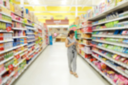 Abstract blurred background of a female customer shopping in a supermarket