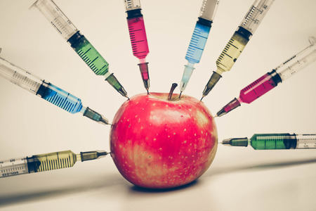 Injecting chemical to apple - gmo fruit Stock Photo