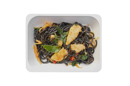 microondas: Espagueti negro con pescado frito, hojas de albahaca y chile Foto de archivo