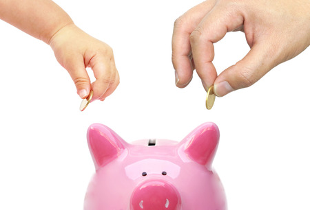 Father and a baby do saving money in a pink piggy bank