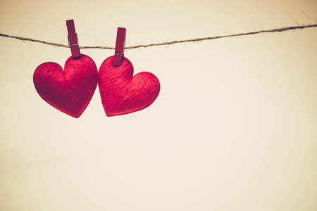 Love for Valentines day - Red hearts hung together on the rope with warm light background