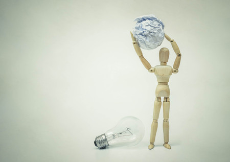 Wood figure mannequins sitting on a crumpled paper ball watching an incandescent light bulb  Business success and failure concept
