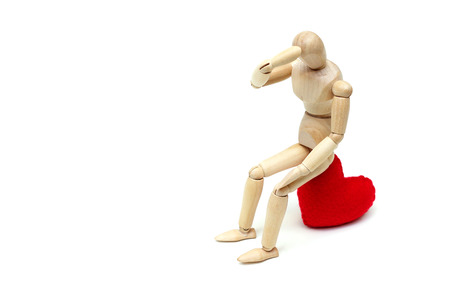 Wood Figure Mannequin sitting sadly on a red heart waiting for love Stock Photo