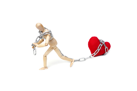 Wood Figure Mannequin using a chain to pull a big red heart Stock Photo