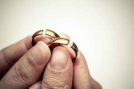 dissappointed: Hand holding broken rings  Divorce cond ending relationship concept Stock Photo