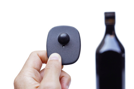 id theft: RFID hard tag isolated - Shoplifting and anti-theft system - Electronic Article Surveillance system used with high-value goods - Alcoholic drinks Stock Photo