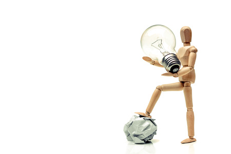 Wood figure mannequins carrying an incandescent light bulb and stepping on a crumpled paper ball  Change  Business with new idea and success concept
