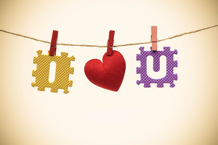 Love for Valentines day - Red heart with I and u jigsaw hung on a rope Stock Photo