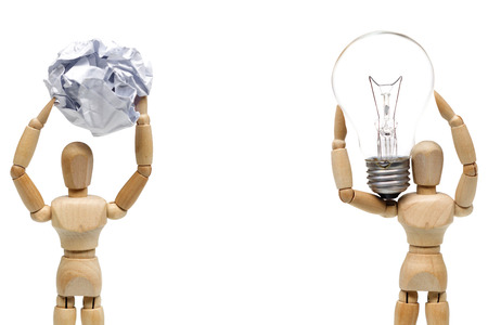 Two wood figure mannequins carrying an incandescent light bulb and a crumpled paper ball  Being smart vs. stupid