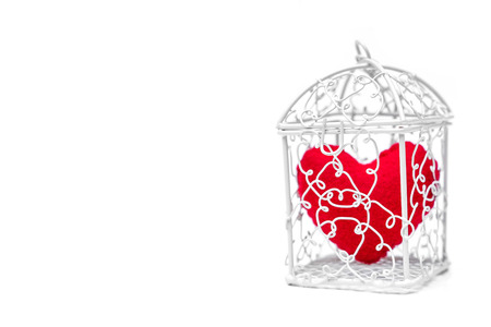 A cage with a red heart inside  Heart in a cage concept Stock Photo