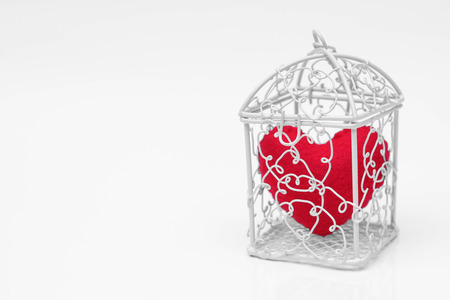 a cage with a red heart inside  Heart in a cage concept