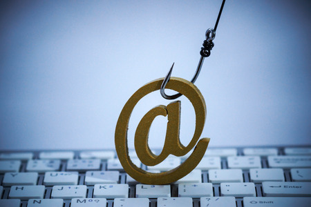 Een vissenhaak met e-mail ondertekent op computertoetsenbord  E-mail phishing aanvalsconcept
