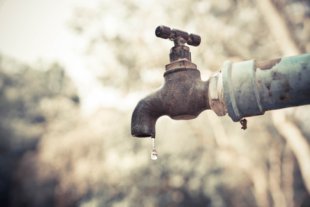 lack of water: A faucet with a water drop  Water consumption concept