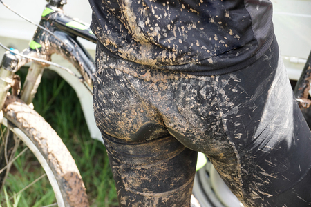 Male cyclist with very dirty bike shorts  Riding on wet and muddy track concept
