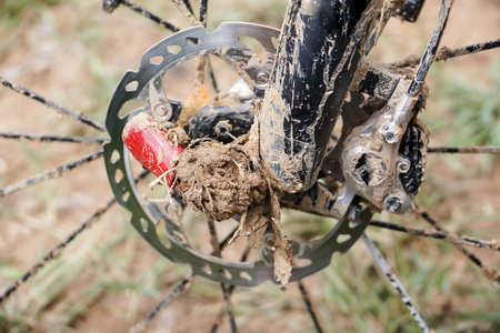 Dirty mountain bike disc brake covered with mud and dirt  Cycling in muddy and wet condition concept Stock Photo