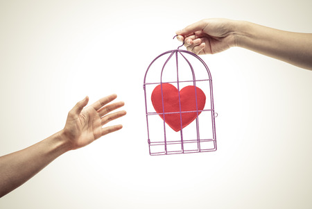 insincere: Female hands giving a bird cage with a red heart inside to a man