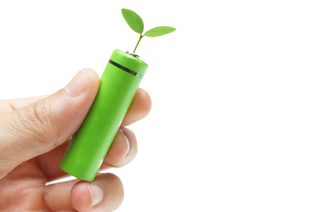 Hand holding a green rechargeable aa battery with a green small plant - Using  environmentally friendly product concept
