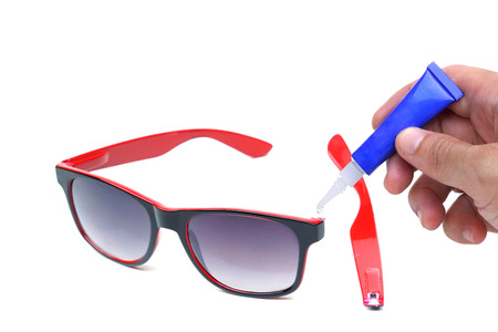 Hand using a glue for repairing a pair of broken sunglasses isolated