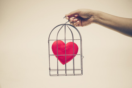 Female hands holding a bird cage with a red heart inside