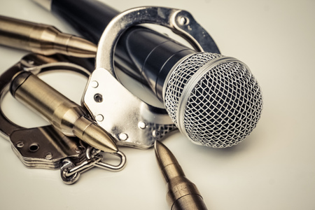 A microphone with handcuffs  Freedom of the press is at risk concept - World press freedom day concept Stock Photo