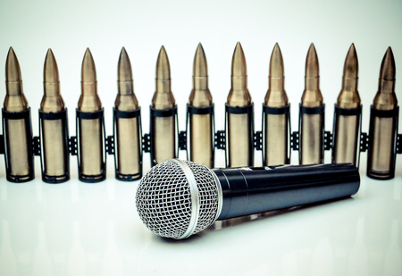unethical: Microphone vs. Bullets  Freedom of the press is at risk concept  World press freedom day concept