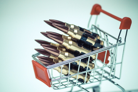 unethical: Rifle bullets on a shopping cart  Illegal weapon sold online in underground market concept